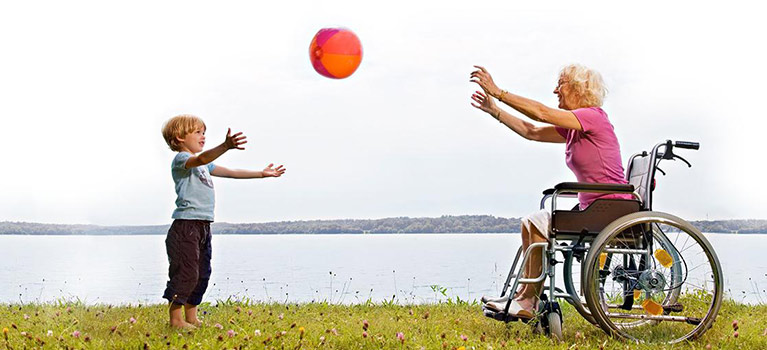 Mature woman in wheelchair playing ball with her grandson