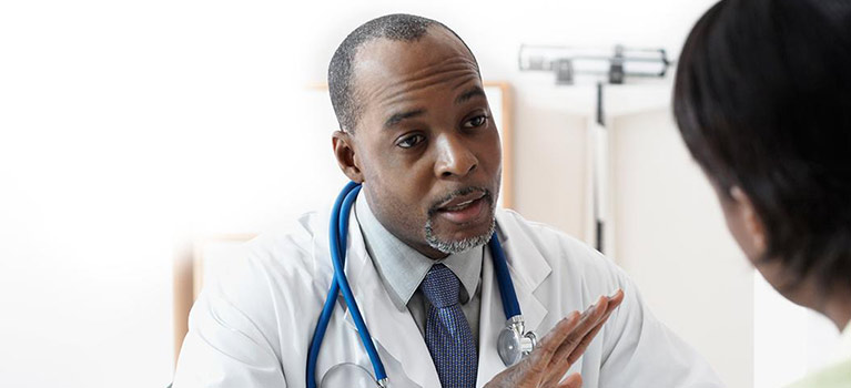 Doctor talking to patient in examining room